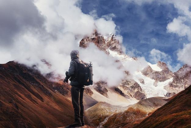 崖の上の写真家。自然は、岩のミラーカメラピークで写真を撮ります。
