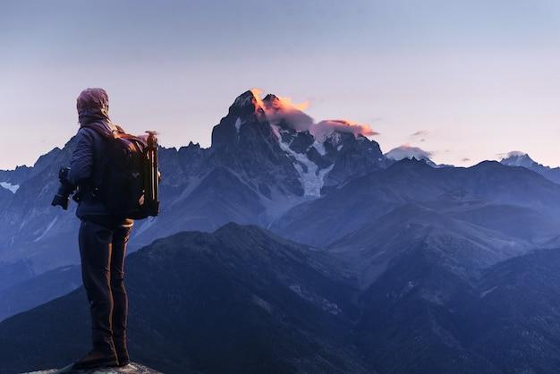 プロの写真家が岩のピーク時に大きなカメラで写真を撮る
