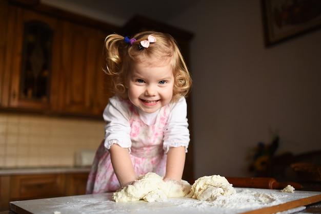 Маленькая девочка замешивает тесто