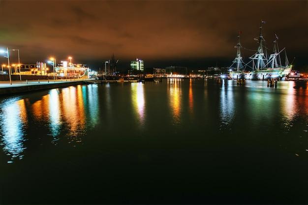 運河の水辺にある建物やボートの夜間照明。