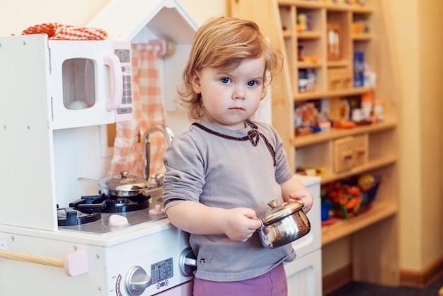 Малышка играет игрушечную кухню