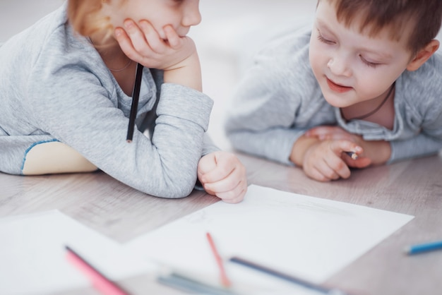 子供たちはパジャマ姿で床に横になり、鉛筆で描きます。鉛筆で描くかわいい子。子供の女の子と男の子の手は、クレヨンで描くとペイントします。クローズアップビュー