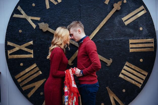 時計の近くに立って美しいスタイリッシュなカップルの肖像画。