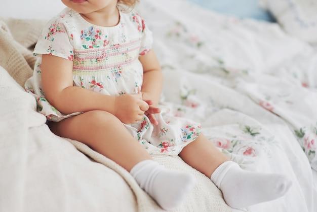 幼年期のコンセプト。家でおもちゃで遊んでベッドでやまかわいいドレスの女の赤ちゃん。白いヴィンテージの子供部屋