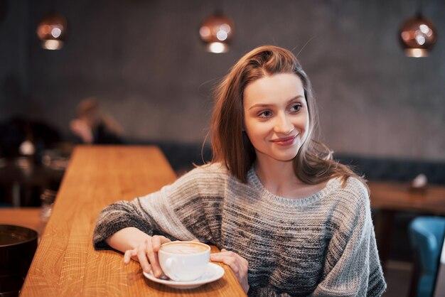 Довольно молодая женщина, сидя в кафе с чашкой чая