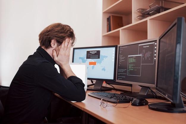 若い危険なハッカーは、機密データをダウンロードしてウイルスを活性化することにより、政府のサービスを破壊します。男は多くのモニターでラップトップコンピューターを使用します