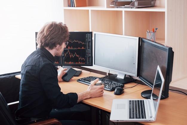 Через плечо виден и биржевой брокер, торгующий онлайн при принятии заказов по телефону. несколько компьютерных экранов с графиками и анализом данных
