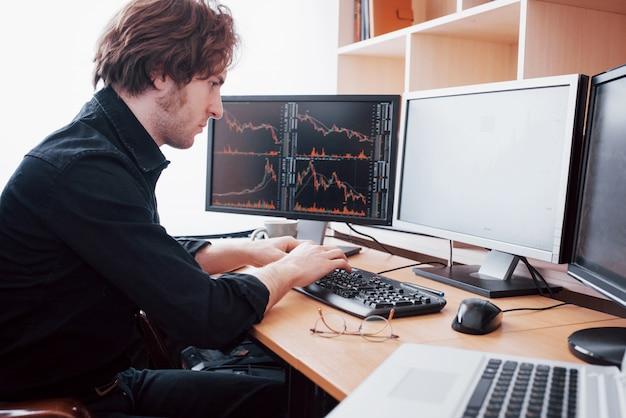 オフィスでのストレスの多い日。クリエイティブオフィスの机に座って彼の顔に手を繋いでいる青年実業家。証券取引所取引外国為替金融グラフィックコンセプト