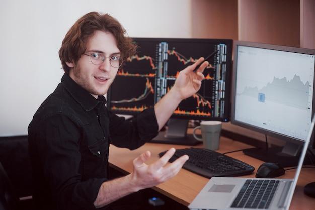 オンラインで株式を取引するビジネスマン。株式ブローカーが複数のコンピューター画面でグラフ、インデックス、数字を見ています。ビジネス成功のコンセプト