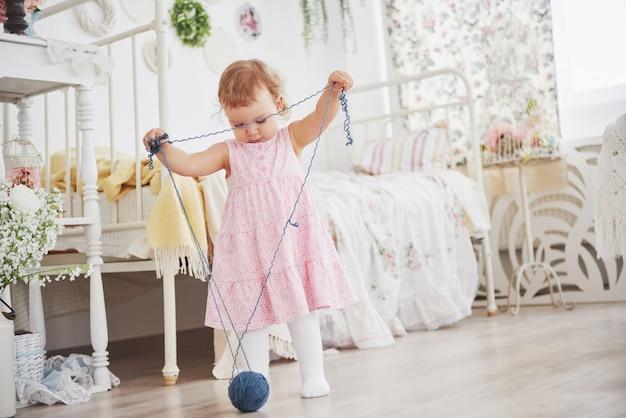 幼年期のコンセプト。かわいいドレスの女の赤ちゃんは、色の糸で遊ぶ。白いヴィンテージの子供部屋