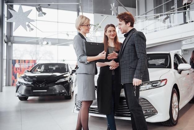Гордые владельцы. красивая молодая пара счастлива обниматься, стоя возле их недавно купленной машине, улыбаясь, радостно показывая ключи от машины