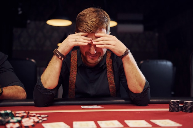 エレガントな若い男がカジノに座って、ポーカーゲームに負けて気分が悪い
