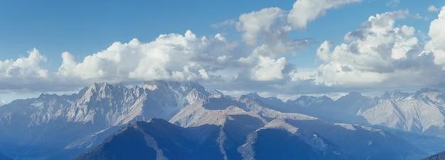 Фантастические заснеженные горы в красивых кучевых облаках