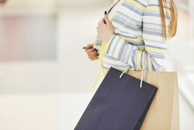 ショッピングの女性。ショッピングで楽しんで買い物袋を持つ幸せな女。消費者、ショッピング、ライフスタイルコンセプト
