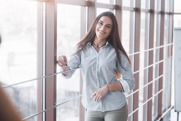 Портрет улыбающегося довольно молодая деловая женщина на рабочем месте