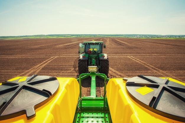 春の植え付けの準備でトラクター耕起農地