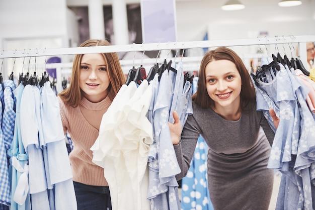 Молодые красивые женщины на еженедельном рынке одежды - лучшие друзья, которые в солнечный день весело проводят время и делают покупки в старом городе - подруги наслаждаются моментами повседневной жизни