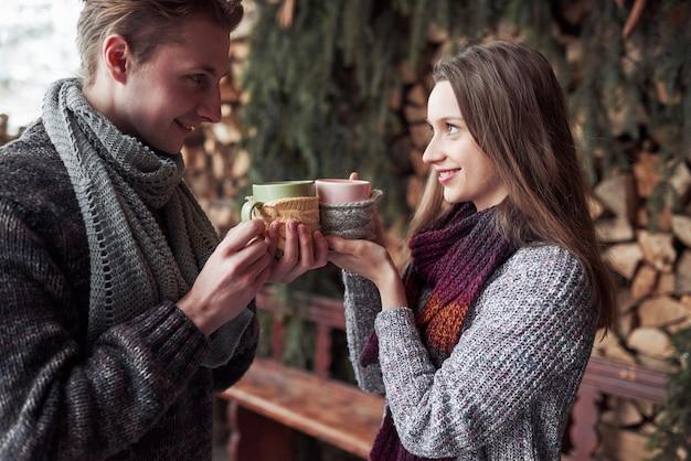 冬の屋外のロマンチックなキャビンで朝食を持っている若いカップル。冬休みと休暇