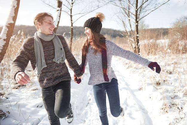 冬の公園で楽しんで幸せな若いカップル。家族の屋外。