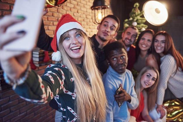 古くからの友人のグループが互いに通信し、自分撮り写真を作成します。新年が来ています。居心地の良い家庭的な雰囲気の中で新年を祝う