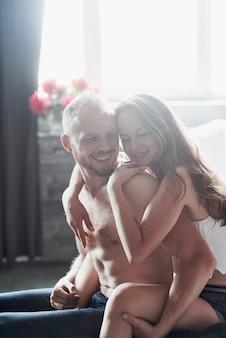 魅力的な若い恋人には、カップルがベッドで一緒に遊んでいて、ホテルの部屋でセクシーなランジェリーを着ています。