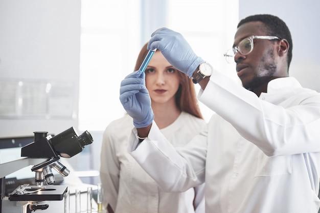 Лабораторные лаборатории проводят эксперименты в химической лаборатории в прозрачных колбах. выходные формулы