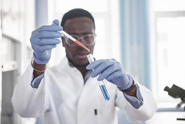 Афро-американский рабочий работает в лаборатории, проводит эксперименты.