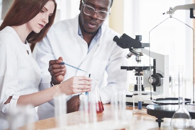 Ученые тесно сотрудничают с микроскопом в лаборатории, проводя эксперименты и анализы.