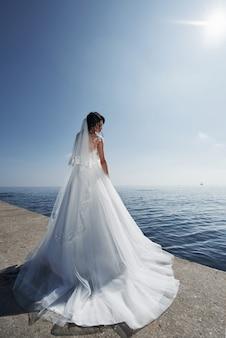 青い空を背景に海沿いのビーチでのウェディングドレスの花嫁