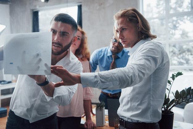 Планирование бизнеса. молодая многорасовая команда в официальной одежде в офисе, глядя на прайс-лист