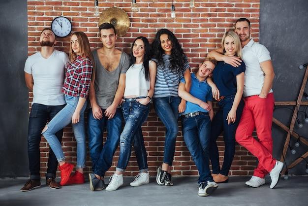 Групповой портрет многоэтнических юношей и девушек в ярких модных одеждах, держащих друг позирует на кирпичной стене