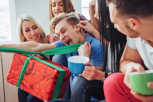 パーティーで親友のグループ。階段の上に座って笑顔で陽気な人々カップコーヒーは誕生日を迎える、素晴らしい贈り物
