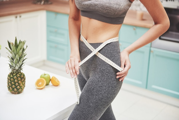 彼女のスリムな体を測定する女性の肖像画。フィットネスと健康的なライフスタイルのコンセプト