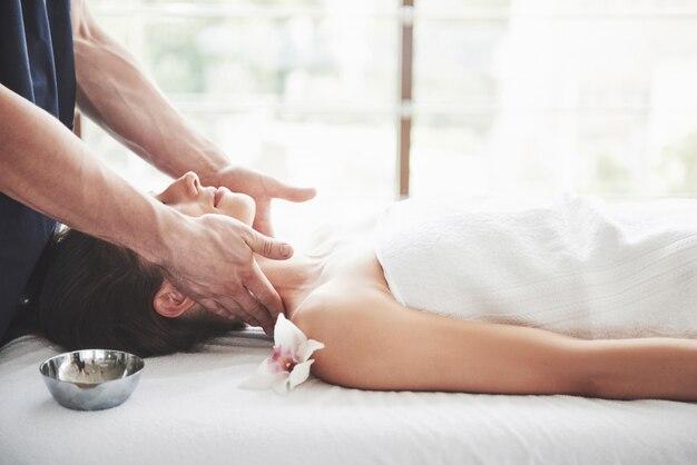 マッサージ師は、女性の首のリラクゼーションマッサージを行います。