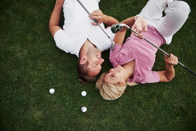 Пара, муж и жена лежат на поле для гольфа и отдыхают после игры