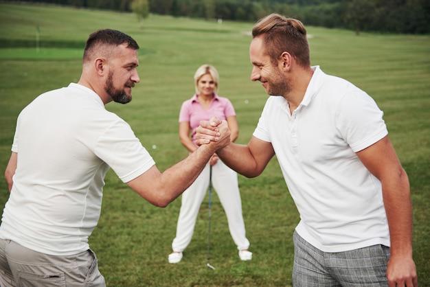 Три игрока играют на поле для гольфа. команда поздравляет и пожимает друг другу руки