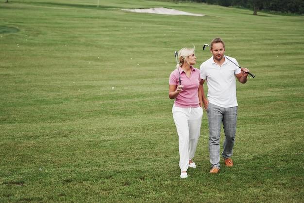 Спортивная пара играет в гольф на поле для гольфа, они стоят до следующей лунки