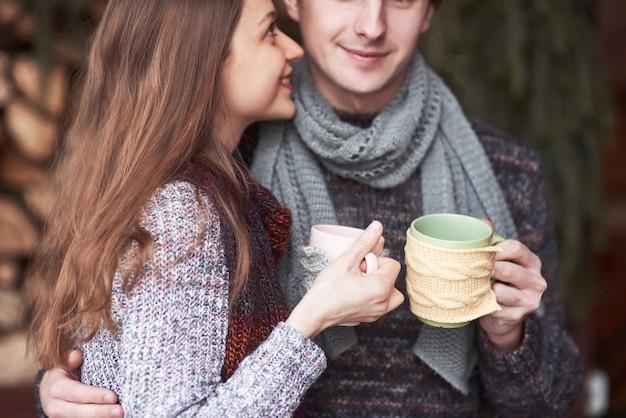 冬の屋外のロマンチックなキャビンで朝食を持っている若いカップル。
