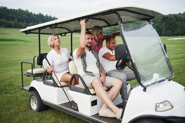 遊ぶ準備をしている若いカップル。笑顔の友人のグループがゴルフカートの穴に来ました