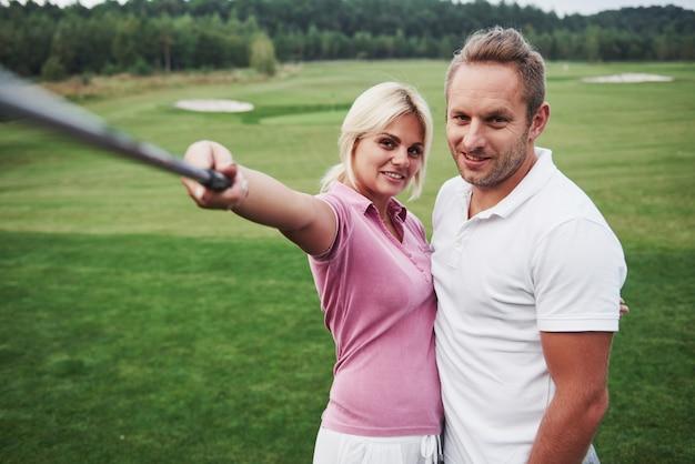 Пара игроков в гольф делает фото на поле для гольфа, используя палку, похожую на сефи полюс
