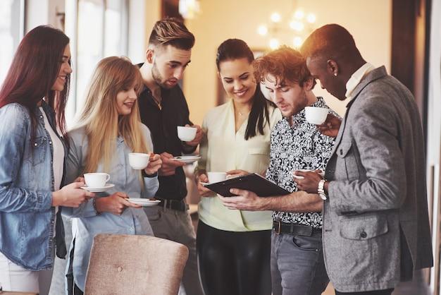 成功するビジネスの人々は、オフィスでのコーヒーブレイク中にガジェットを使用し、話し、笑っている