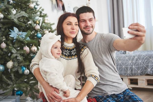 Семья собралась вокруг елки, используя планшет