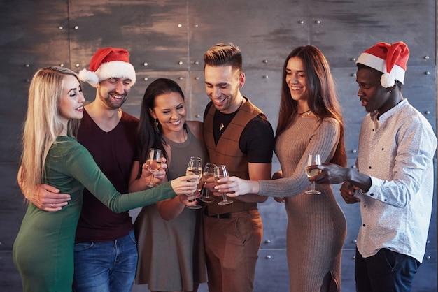 Новый год наступает! группа веселых молодых многонациональных людей в санта шляпы на вечеринке, представляя концепцию эмоциональный образ жизни людей