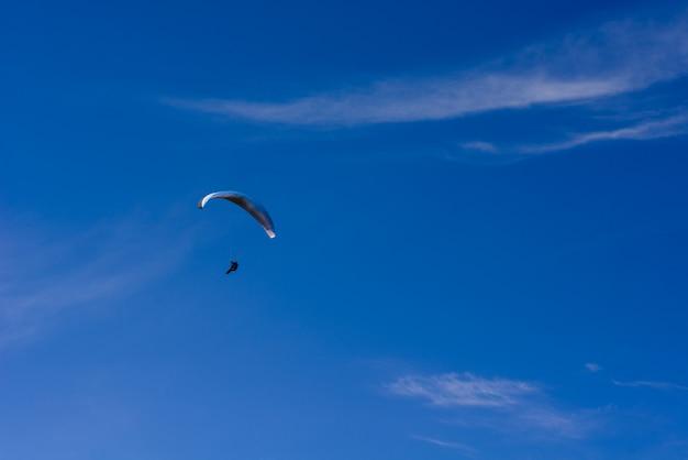 Человек на парашюте летит в ясном небе