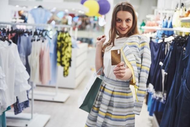 ショッピングの女性。ショッピングバッグやショッピングで楽しんでいるクレジットカードと幸せな女。消費者、ショッピング、ライフスタイルコンセプト