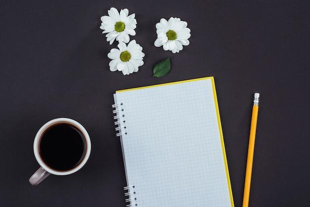 На черном блокноте карандаш, ароматный кофе и белые цветы.