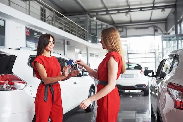 自動車ビジネス、車の販売、取引、ジェスチャー、人々の概念-ディーラーがオートショーやサロンで新しい所有者にキーを与えるのクローズアップ