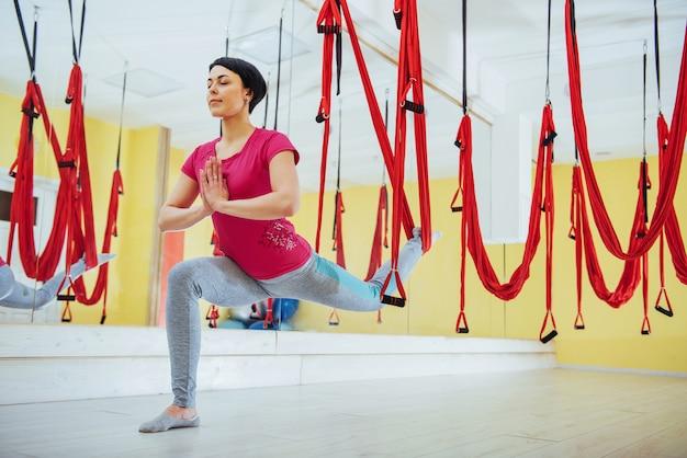 Молодая красивая женщина практикующих йогу муха с гамаком. полеты, фитнес, стрейч, баланс, физические упражнения.