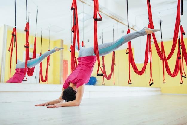反重力ヨガの練習を行う若い女性