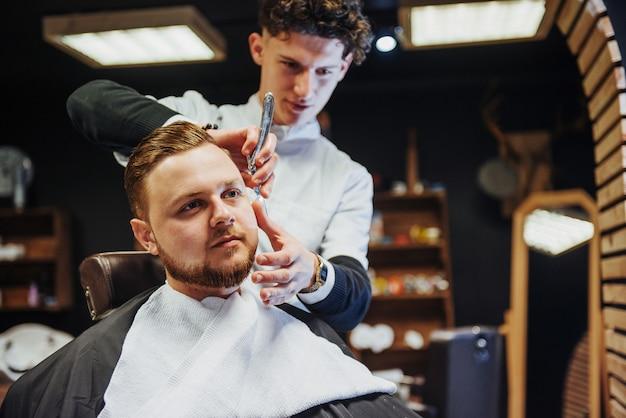 Мужчина-парикмахер делает стрижку бороды взрослым мужчинам в мужской парикмахерской